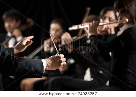 Conductor directing symphony orchestra with performers on background. poster