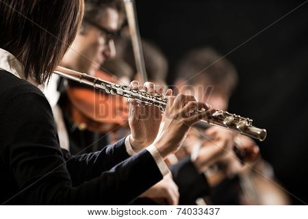 Female Flutist With Orchestra On Stage