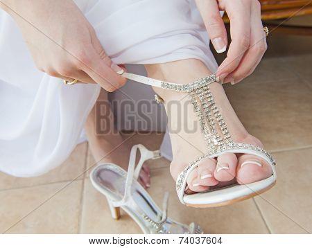 Bride Putting On Wedding Sandals