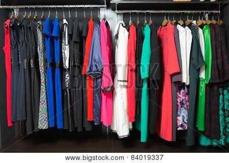 Colorful women's dresses on hangers in a retail shop poster