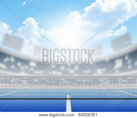 A tennis court in an arena with a marked hard blue surface in the daytime under a blue sky poster