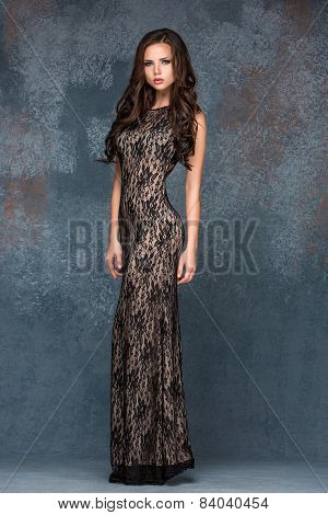 Beautiful young brunette woman with her hair posing in a i long dress. Studio, on gray background
