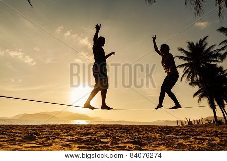 Teenage Couple Balancing Slackline On The Beach