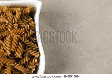 White Dish Filled With Uncooked Wholewheat Fusilli Pasta