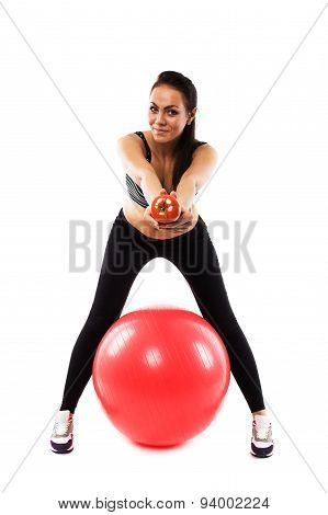 Slim Girl Wearing Training Suit With Gym Ball Offering A Tomato