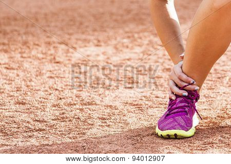Running sport injury - twisted broken ankle. Female athlete runner touching foot in pain due to spra