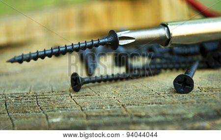 Screws and screwdriver on wooden background.
