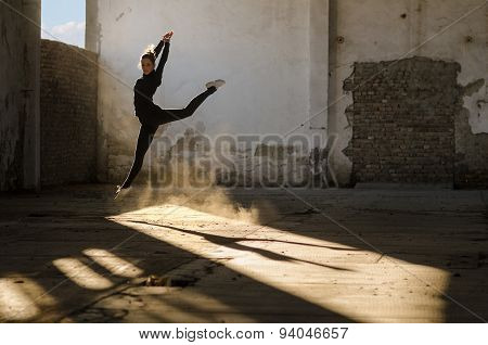Beautiful young ballerina dancing in abandoned building