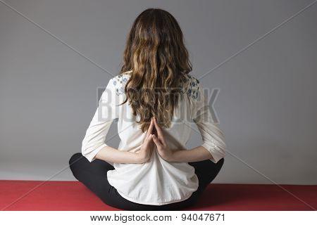 Woman doing reverse namaste pose on grey background. poster