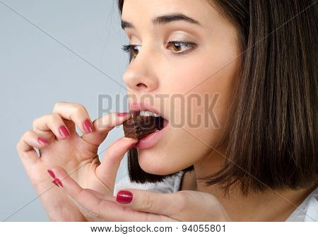 Portrait Of Beautiful Girl Eating Chocolate Cookies Isolated On Gray Background