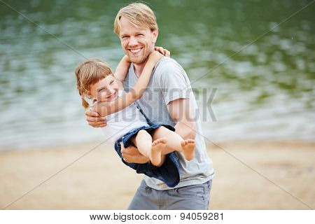 Father and daughter playing and romping on beach in summer