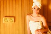 Beauty health spa concept. Woman relaxing in sauna interior looking on equipment thermometer and hygrometer. poster