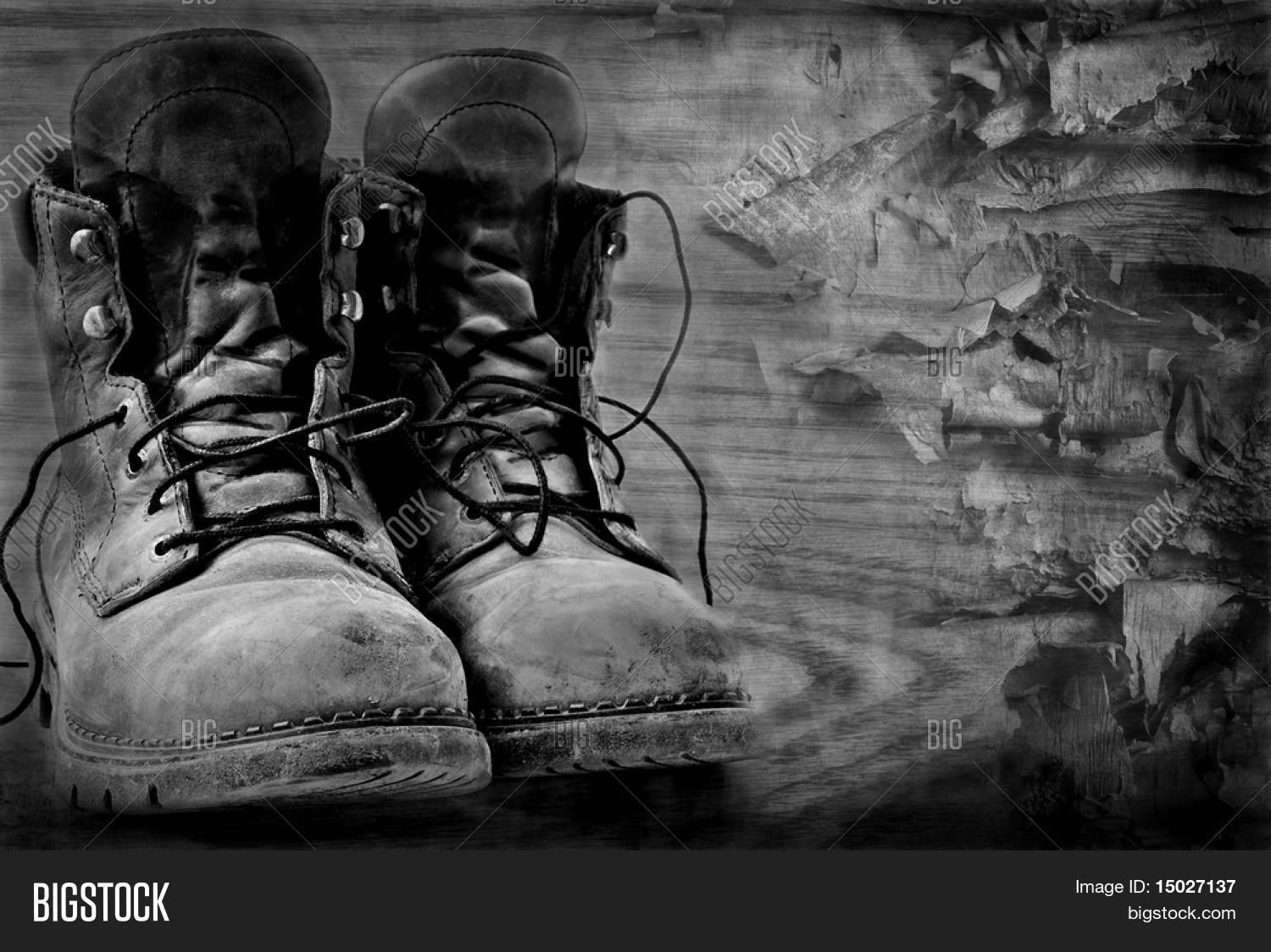 Artistic black and white image of rugged boots on wood textured background