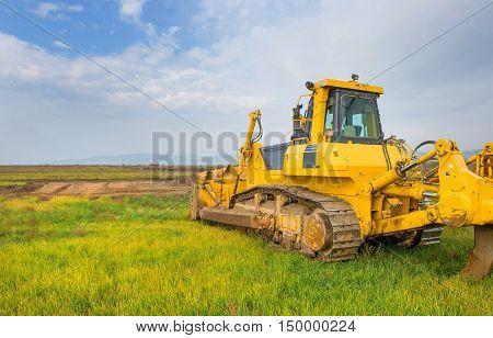 Big yellow modern bulldozer in the green field