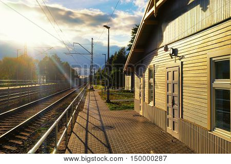 The wooden building of the railway station in the rays of the setting sun over the lines of iron rails and green trees