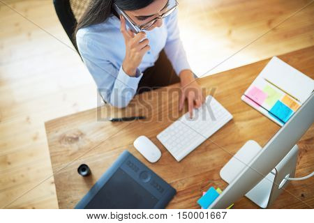 Young businesswoman taking a mobile call as she surfs the internet on her desktop computer at a neatly organised desk viewed from above