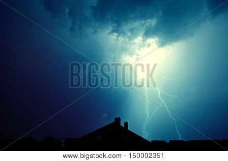 Dramatic sky and storm. Lightning hit the house. Power of nature concept.