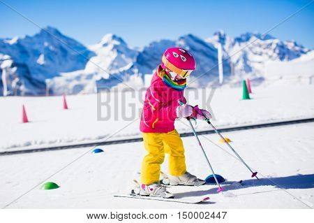 Child in alpine ski school with magic carpet lift and colorful training cones going downhill in the mountains on a sunny winter day. Little skier kid learning and exercising backwards skiing on slope.