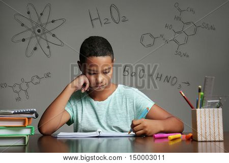 Afro-American boy studying at table. Chemical formulas on gray background. Education concept.