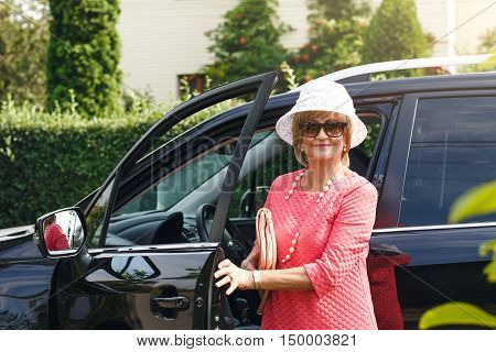 Attractive well-dressed senior lady in sunglasses and hat came by car