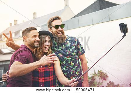 Friends make funny faces as they take photo beside white wall with plants growing against it