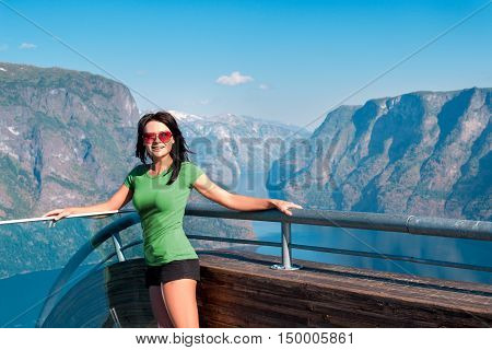 Woman tourist on Stegastein Viewpoint in a summer sunny day, Flam, Norway