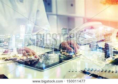 Doctor working with tablet only hands seen. Phonendoscope and phone on table. Office. Concept of work. Toned image. Double exposure