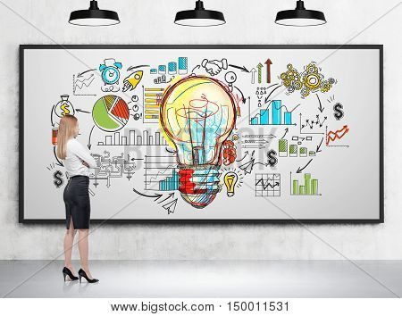 Girl with blond hair is looking at large light bulb and startup sketch on whiteboard in room with concrete walls and lamps. Concept of the next big thing