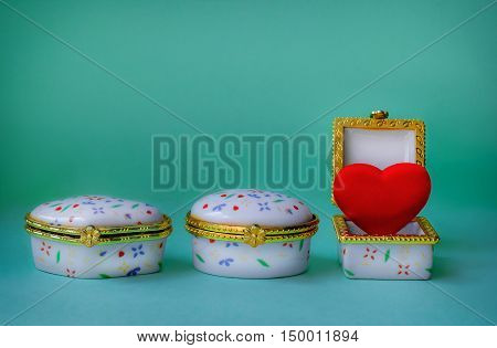 Jewelry boxes with one having a red heart inside on blue background