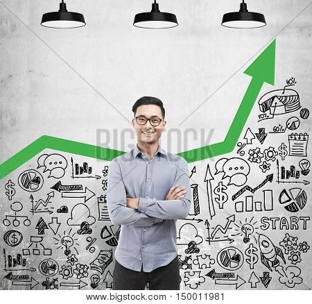 Confident Asian businessman is posing near concrete wall with green graph and startup icons. Concept of stock market. Mock up