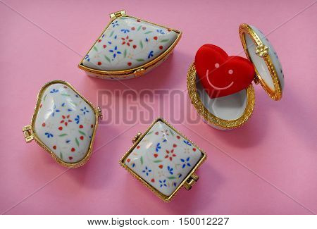 Jewelry boxes with one having a red smiley heart inside on pink background, top view