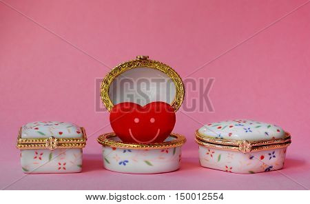 Jewelry boxes with one having a red smiley heart inside on pink background