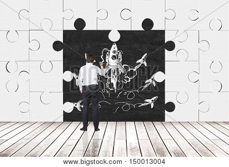 Rear view of businessman drawing rocket sketch on blackboard in room made of puzzle pieces. Concept of grotesque