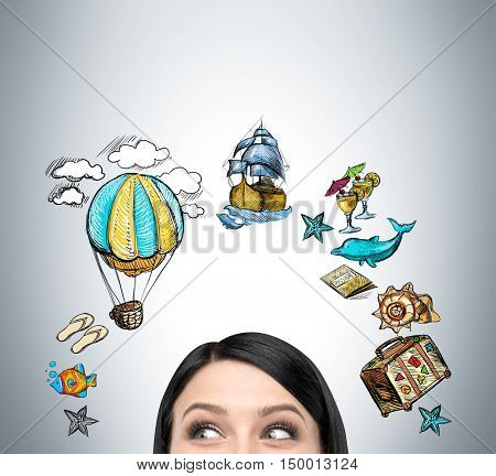 Close up of girl's head against gray wall with ancient transportation devices and travel icons. Concept of time travelling