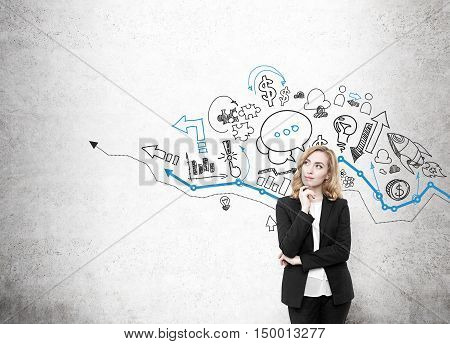 Girl with red hair standing near concrete wall with blue graph and icons. Concept of consulting. Mock up
