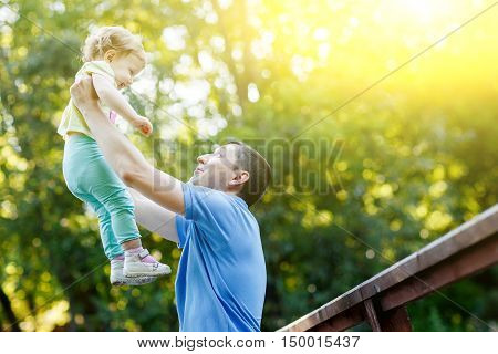 Young father holds little daughter in arms in park .Image with lens flare effect