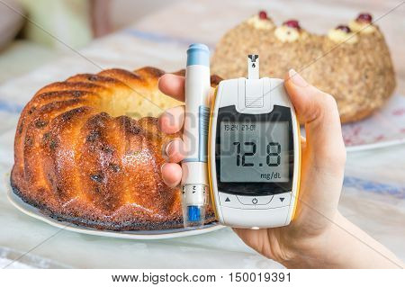 Diabetes, Diet And Unhealthy Eating Concept. Hand Holds Glucomet