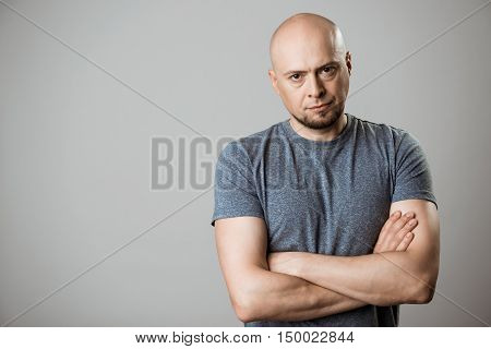 Displeased young man looking at camera with crossed arms over beige background. Copy space.