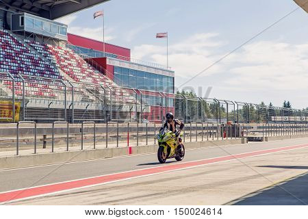 Moscow region, Russia - 27 August : route Moscow raceway motorcycle racer in a green suit and helmet, riding a motorcycle around the pits to practice in day of Russian cinema 27 August, 2016.