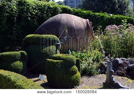 Enormous amphora serving as fountain in the middle of box tree and in the middle of a lawn.