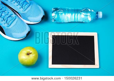 Sneakers, bottled water, apple and clean chalkboard on blue background. Concept of healthy lifestile and food, everyday training and force of will.