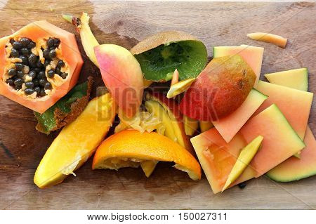 A variety of fruit skins and scraps on a wood cutting board ready to be thrown in the compost pile in the garden.