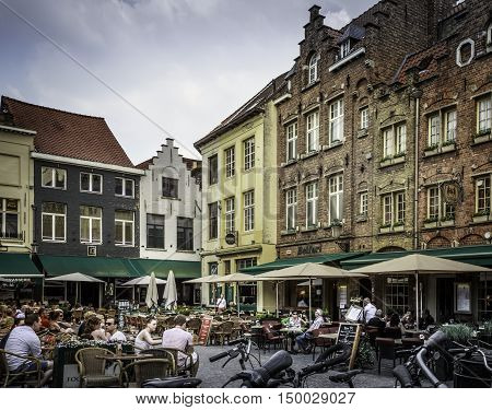 BRUGES, BELGIUM - MAY 12, 2016: People relaxing at an outdoor food court. Bruges is a popular tourist destination because of it's historical significance and proximity to Flanders Fields.