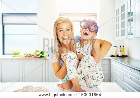 Laughing little girl wearing huge purple plastic glasses sitting barefoot on the kitchen counter being hugged by her adoring mother