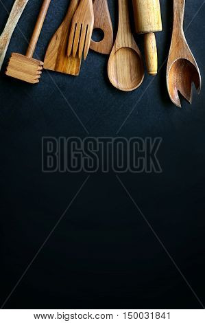 A collection of vintage wooden cooking utensils spoons rolling pin masher spatula are framing the top border of a black slate chalkboard.
