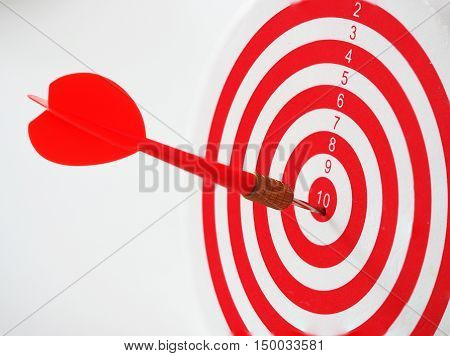 Red bullseye dart arrow hitting target center of dartboard. Concept of success target goal achievement. (selective focus)