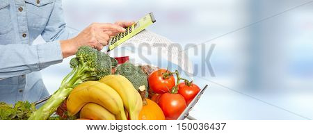 Woman hands with grocery receipt and calculator.