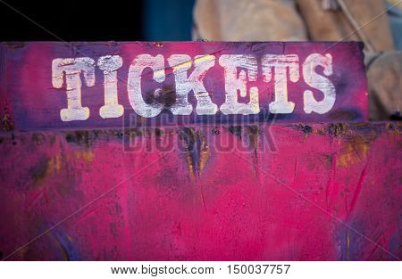 Colorful red and white sign with tickets on it