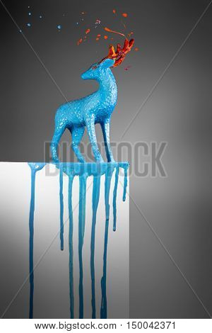 Magic blue deer with melting horns on white postament