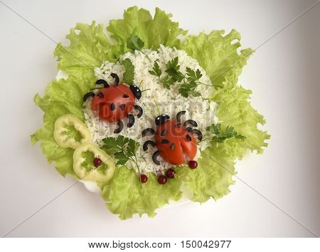 Ladybugs are made of tomatoes and olives. Ridiculous food for good mood. Ladybugs are located on lettuce leaves.